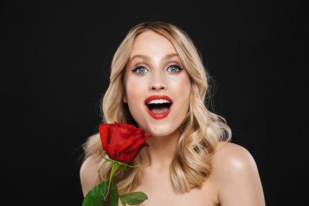 Porträt einer hübschen jungen schockierten blonden frau mit den roten lippen des hellen make-ups, die lokalisierte holdingrosenblume aufwerfen.