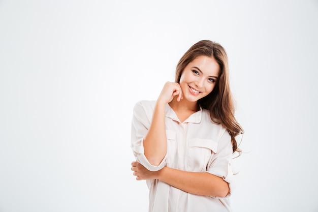 Porträt einer hübschen lächelnden frau posiert isoliert auf einer weißen wand