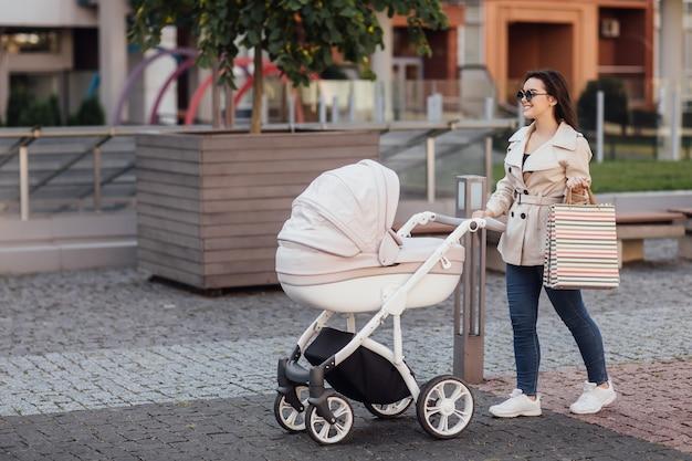 Porträt einer hübschen mutter mit einkaufspaket, die mit kinderwagen im stadtzentrum spazieren geht
