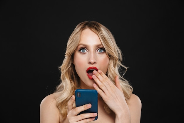 Porträt einer hübschen schockierten jungen blonden frau mit den roten lippen des hellen make-ups, die lokalisiert unter verwendung des handys aufwerfen.
