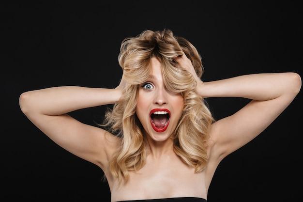 Porträt einer hübschen schockierten jungen blonden frau mit der roten lippenaufstellung des hellen make-ups lokalisiert.