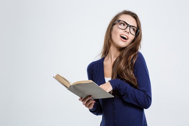Porträt einer hübschen studentin, die ein buch hält und wegschaut auf exemplar isoliert auf weißem hintergrund