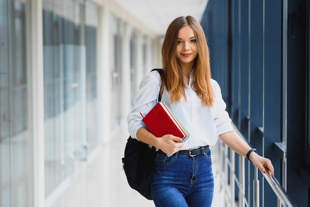 Porträt einer hübschen studentin mit büchern und einem rucksack im flur der universität