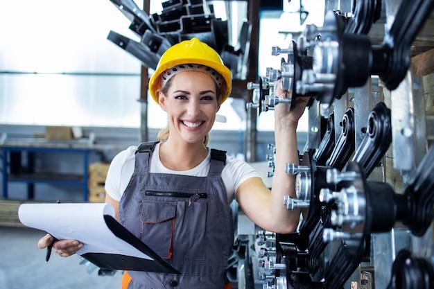 Porträt einer industriearbeiterin in arbeitskleidung und helm, die in der fabrikproduktionslinie steht