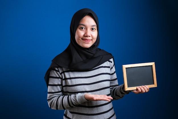 Porträt einer intelligenten, glücklichen, erfolgreichen asiatischen muslimischen frau mit hijab, die in die kamera lächelt, während sie eine leere tafel oder eine kreidetafel mit kopienraum hält und zeigt