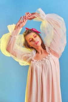 Porträt einer isolierten jungen frau in einem schönen hellen kleid auf einem blauen hintergrund. hände in einer schönen bewegung erhoben.