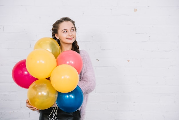 Porträt einer jugendlichen, welche die ballone in der hand stehen gegen weiße wand hält