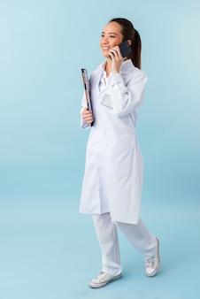 Porträt einer jungen ärztin, die isoliert über der blauen wand posiert, die zwischenablage hält, die durch handy spricht.