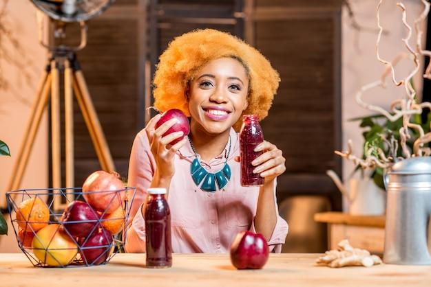 Porträt einer jungen afrikanerin mit frischen roten früchten und smoothies, die drinnen im gemütlichen zuhause sitzen
