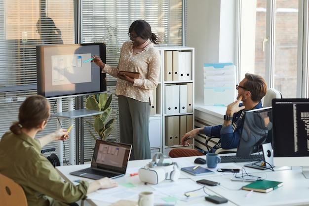 Porträt einer jungen afroamerikanischen frau, die auf einen digitalen bildschirm zeigt, während sie bei einer teambesprechung im softwareproduktionsbüro eine präsentation hält, kopierraum