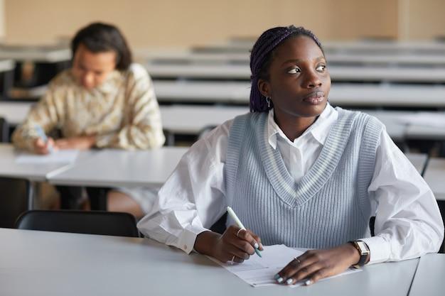 Porträt einer jungen afroamerikanischen frau, die in der schulaula eine prüfung ablegt und nachdenklich wegschaut, platz kopieren