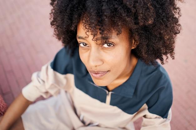 Porträt einer jungen afroamerikanischen frau, die mit ernstem gesichtsausdruck in die kamera schaut