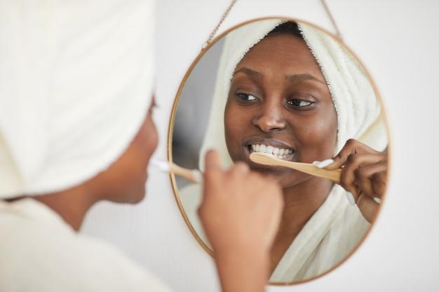 Porträt einer jungen afroamerikanischen frau, die morgens die zähne putzt und in den spiegel schaut, kopienraum