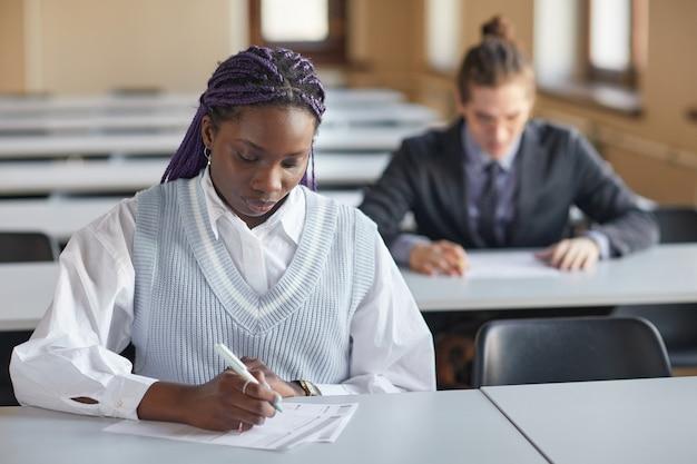 Porträt einer jungen afroamerikanischen frau, die schuluniform trägt, während sie die prüfung im auditorium der hochschule ablegt, kopienraum