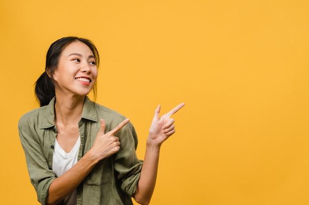 Porträt einer jungen asiatischen dame, die mit fröhlichem ausdruck lächelt, zeigt etwas erstaunliches an leeren stellen in freizeitkleidung und steht isoliert über gelber wand. gesichtsausdruck konzept.