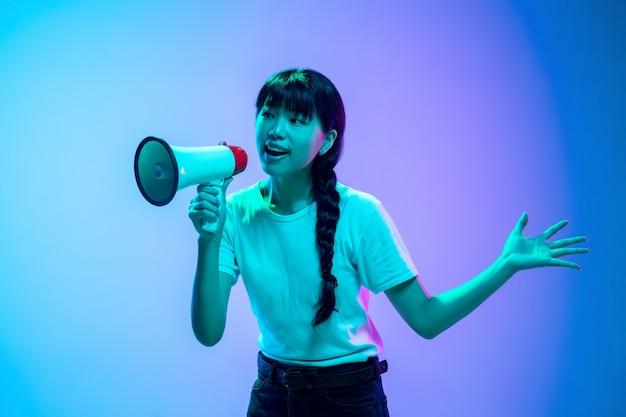Porträt einer jungen asiatischen frau auf blau-violettem farbverlauf im neonlicht