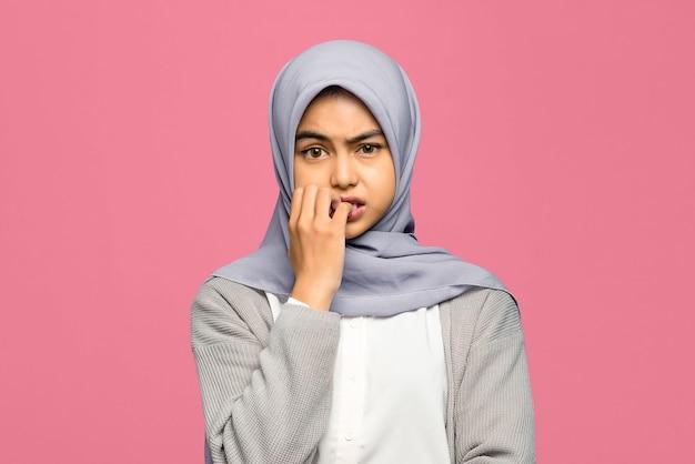 Porträt einer jungen asiatischen frau, die ihre nägel beißt und sich um etwas sorgen macht