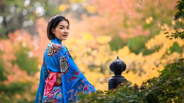 Porträt einer jungen asiatischen frau, die japanische blaue kimono-modegeschichte trägt, die in der herbstsaison in japan im park steht