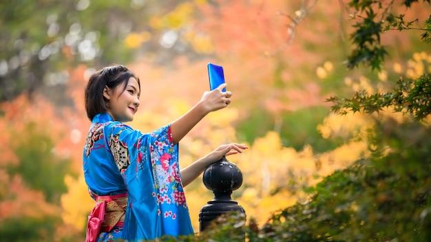 Porträt einer jungen asiatischen frau, die japanische blaue kimono-modegeschichte trägt, die selfie per smartphone im park in der herbstsaison in japan steht