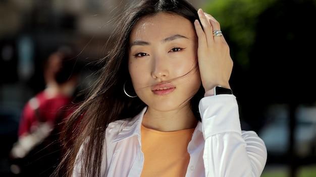 Porträt einer jungen asiatischen frau in lässig gekleidet, die draußen auf der straße zur kamera schaut