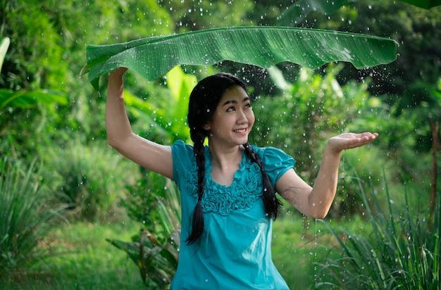 Porträt einer jungen asiatischen frau mit schwarzen haaren, die ein bananenblatt halten