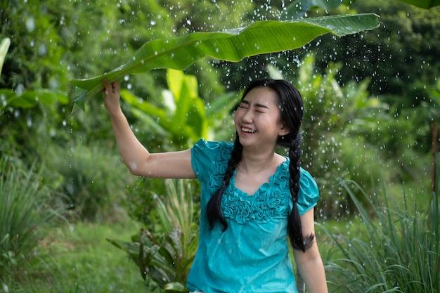 Porträt einer jungen asiatischen frau mit schwarzen haaren, die ein bananenblatt im regen halten