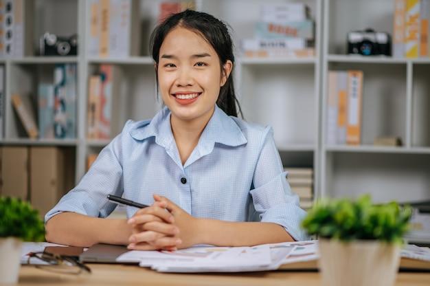 Porträt einer jungen asiatischen freiberuflerin, die mit papieren am arbeitsplatz im homeoffice arbeitet, während der quarantäne-kovid-19-selbstisolation zu hause, von zu hause aus arbeiten konzept