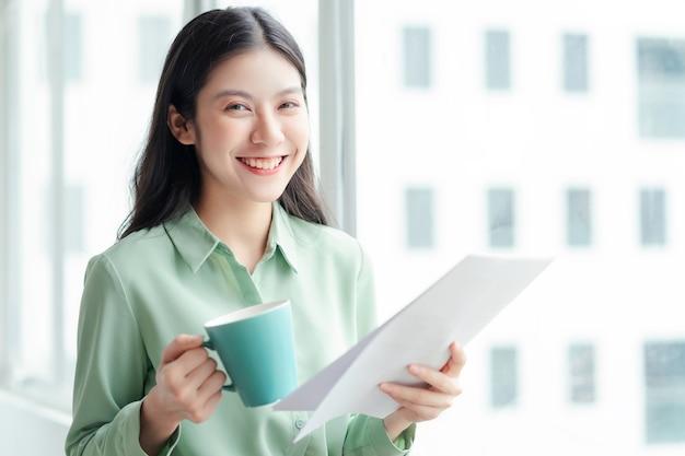 Porträt einer jungen asiatischen geschäftsfrau, die mit fröhlichem ausdruck an der glastür steht