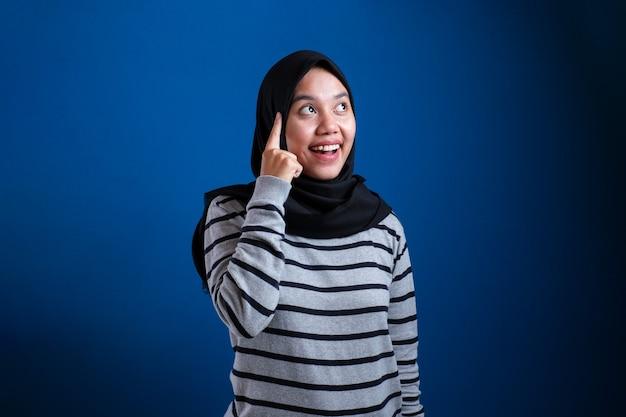 Porträt einer jungen asiatischen muslimischen frau, die mit dem finger nach oben zeigt und lächelt und eine gute idee hat, isoliert auf blauem hintergrund