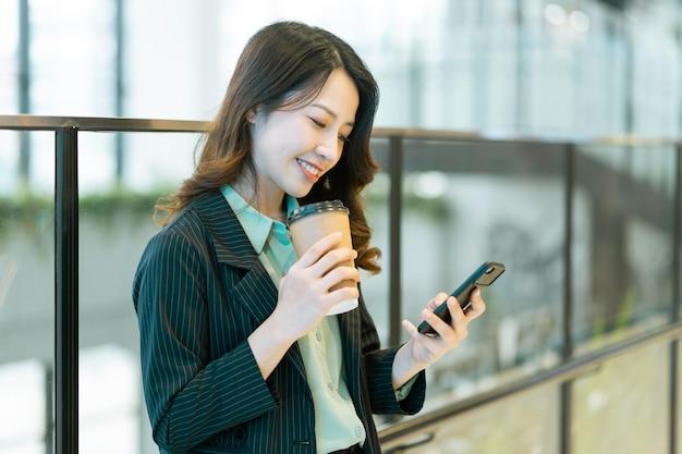 Porträt einer jungen asiatischen regisseurin, die steht, kaffee trinkt und auf das telefon hört