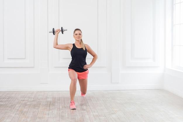 Porträt einer jungen athletischen, schönen bodybuilderin in rosa shorts und schwarzem oberteil, die kniebeugen macht und im fitnessstudio mit den hanteln an der weißen wand trainiert. indoor, studioaufnahme, blick in die kamera