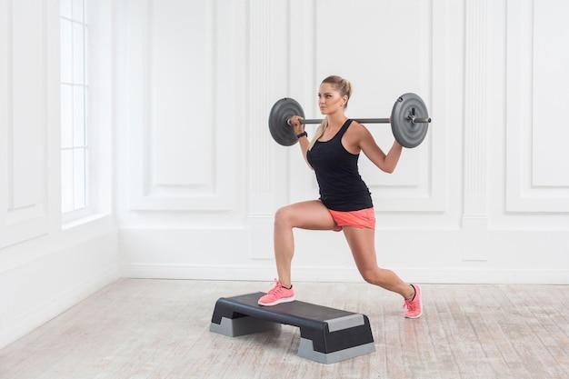 Porträt einer jungen athletischen, schönen bodybuilderin in rosa shorts und schwarzem oberteil, die langhantel auf den schultern hält und kniebeugen mit einem bein auf schritt im fitnessstudio an der weißen wand macht. indoor, studioaufnahme