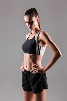 Porträt einer jungen attraktiven fitnessfrau, die aufwirft