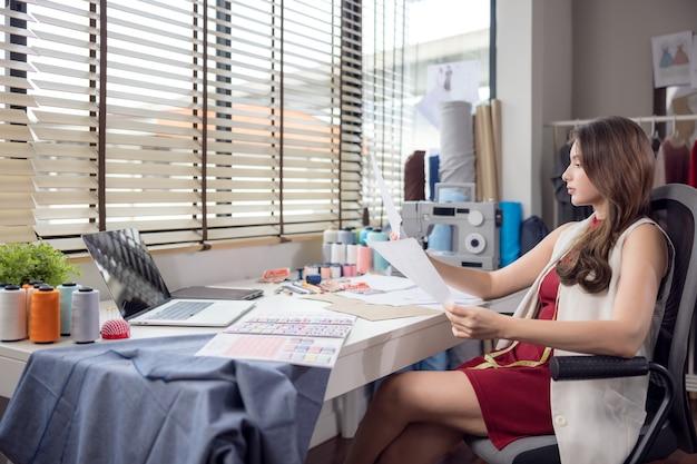 Porträt einer jungen, attraktiven frau auf dem tisch eines stilvollen modedesigners, umgeben von farbigen textilmustern. attraktive frau, die in einem modestudio mit mannequins und bunten tüchern arbeitet.