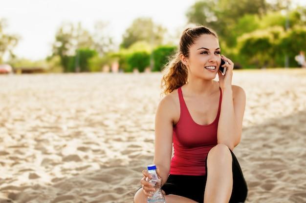 Porträt einer jungen attraktiven frau, die am handy beim sitzen auf dem strand spricht