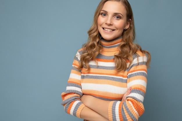 Porträt einer jungen attraktiven, glücklich lächelnden blonden frau mit welligem haar, die gestreift trägt