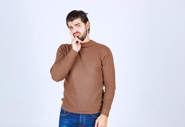 Porträt einer jungen attraktiven mannmodellstellung und -denkens.