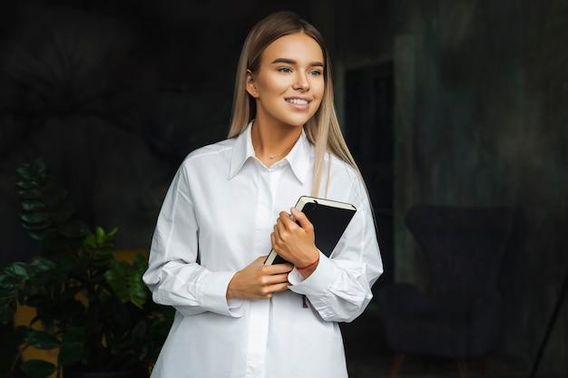 Porträt einer jungen attraktiven mitarbeiterin während eines geschäftstreffens im büro, steht vor der kamera und hält einen notizblock in den händen.