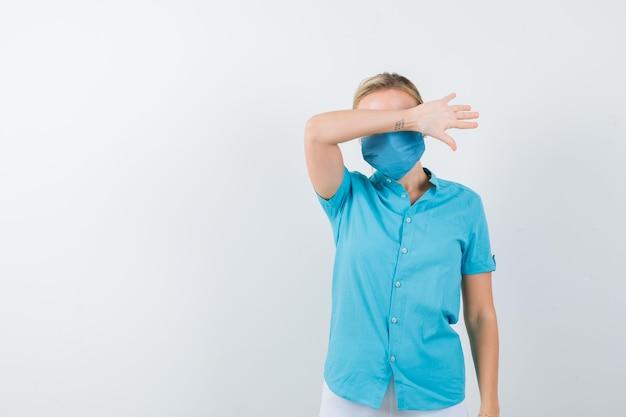 Porträt einer jungen blonden frau, die die augen mit dem arm in freizeitkleidung bedeckt, isoliert