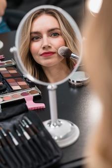 Porträt einer jungen blonden frau, die kosmetik verwendet