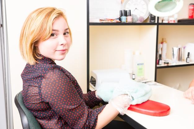 Porträt einer jungen blonden frau, die während der parrafin-wachs-spa-behandlung mit in frotteehandschuhe gewickelten händen am tisch sitzt und im salon über die schulter in die kamera blickt