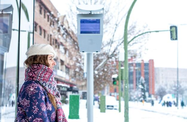 Porträt einer jungen blonden frau in winterkleidung, die an der bushaltestelle sitzt. schnee in der stadt.