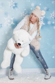 Porträt einer jungen blonden frau mit langen haaren in winterkleidung in einer umarmung mit einem großen eisbären