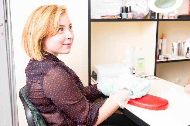 Porträt einer jungen blonden lächelnden frau, die während der parrafin-wachs-spa-behandlung mit in frotteehandschuhe gewickelten händen am tisch sitzt und glücklich und entspannt aussieht