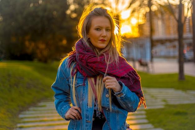 Porträt einer jungen blondine mit einer jeansjacke auf einem sonnenuntergang