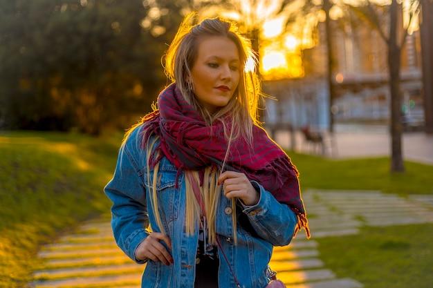 Porträt einer jungen blondine mit einer windjacke mit sonne im hintergrund bei sonnenuntergang