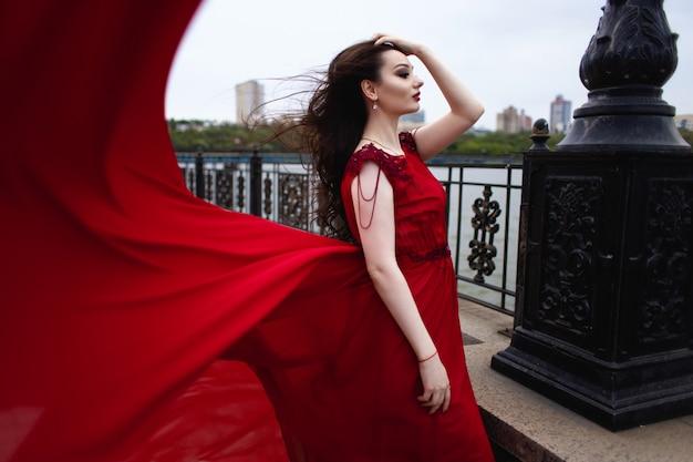 Porträt einer jungen brünetten frau in einem roten kleid mit einem zug