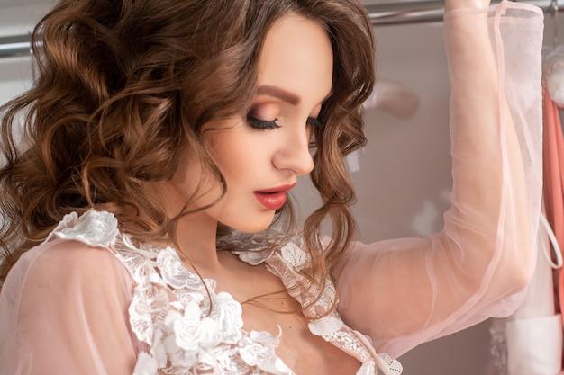 Porträt einer jungen charmanten dame mit schönem make-up und lockigem haar