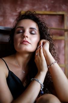 Porträt einer jungen charmanten frau mit lockigem haar, hellhäutigem mädchen in einem schwarzen top und mit einem lächeln im gesicht