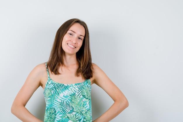 Porträt einer jungen dame, die die hände in der bluse auf der hüfte hält und fröhliche vorderansicht sieht